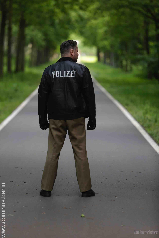 SM Master Domonus Berlin alias Master Andre in einem Park in Rueckansicht bekleidet mit einer Polizeiuniform