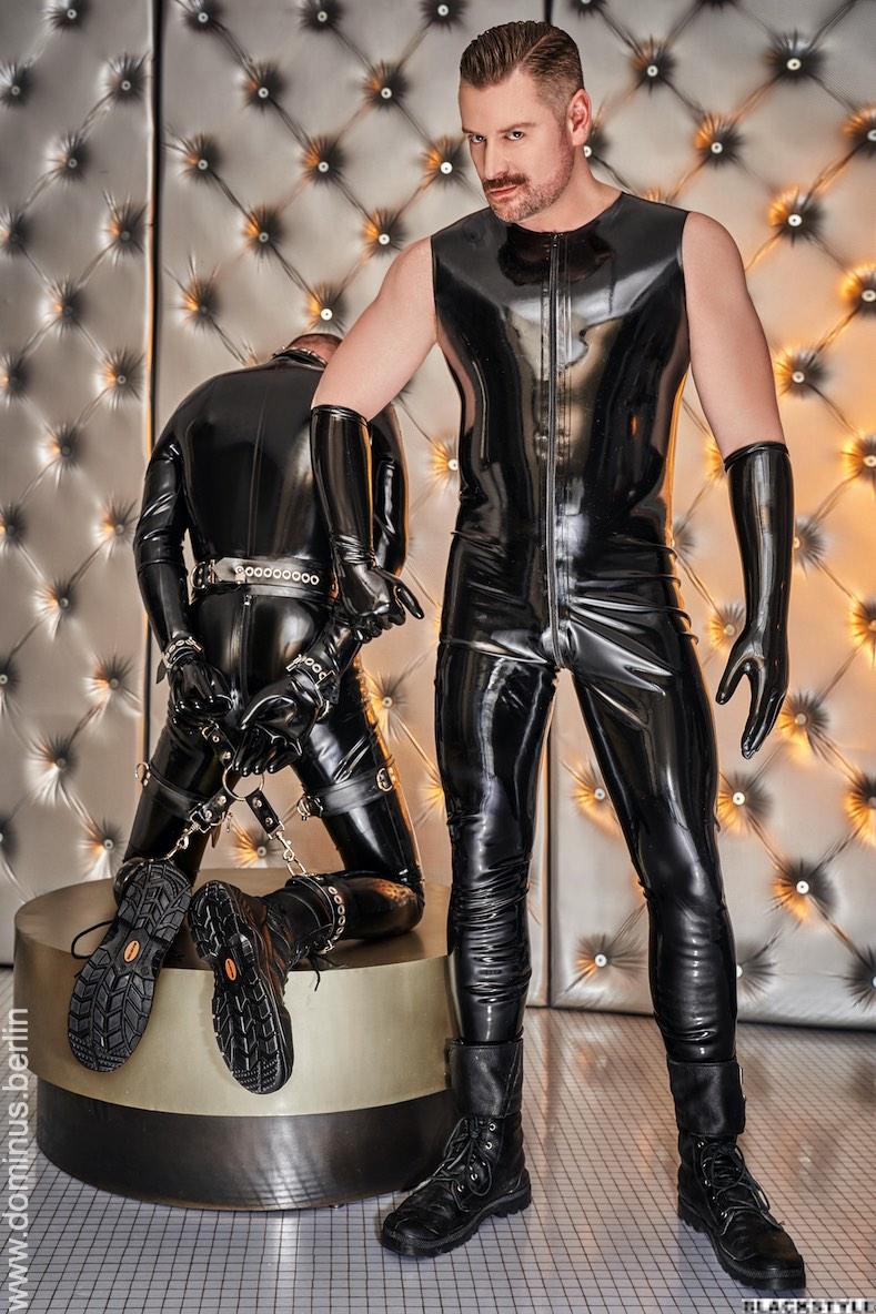 BDSM Master Andre alias Dominus Berlin in Ganzkoerper Latex mit Handschuhen frontal mit Sklave in Rubber und Fesseln an Hand und Fuss