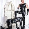 BDSM Master Andre alias Dominus Berlin in schwarzem Latex mit Handschuhen in einem weissen Thronsaal mit Sklave auf Knien im Rubberanzug und Hundemaske an einer Hundeleine gefuehrt und in Demut