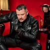 SM Master Dominus Berlin alias Master Andre in Vollleder in einem rotem Sessel und Lampe mit Sklave Des Dominus Diener und Champagner in Demut und als Diener
