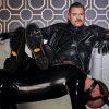BDSM Master Dominus Berlin alias Master Andre in Lederuniform auf weißem Sofa die Fuesse auf den Sklaven Des Dominus Diener in Latex gelegt