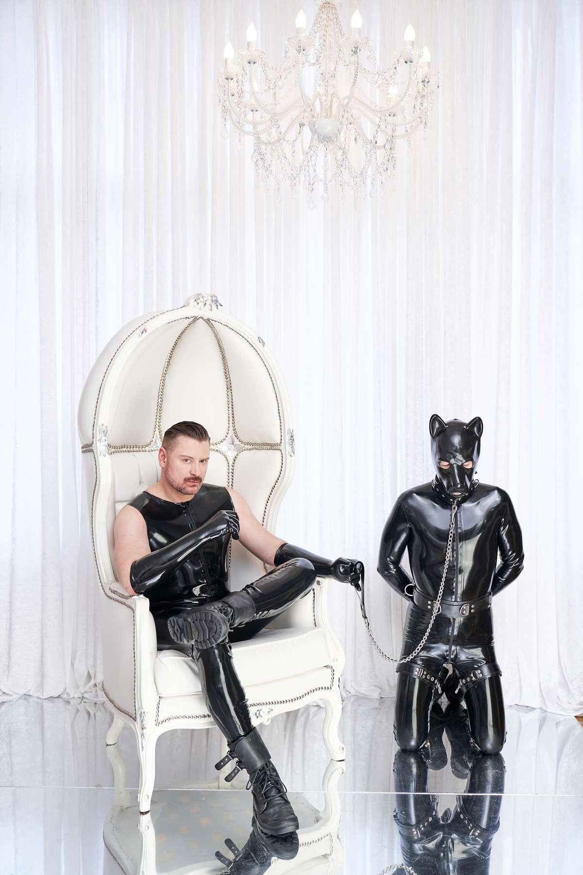Luxus Umgebung in Weiß mit Kandelaber und Thron Sessel mit SM Master Andre alias Dominus.Berlin in Rubber und Hunde Sklave DesDominusDiener in Latex Outfit an Kette