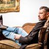 Fetisch Master Dominus Berlin alias Master Andre in Sakko Jeans und Cowboy Stiefeln Sendras auf Sofa sitzend