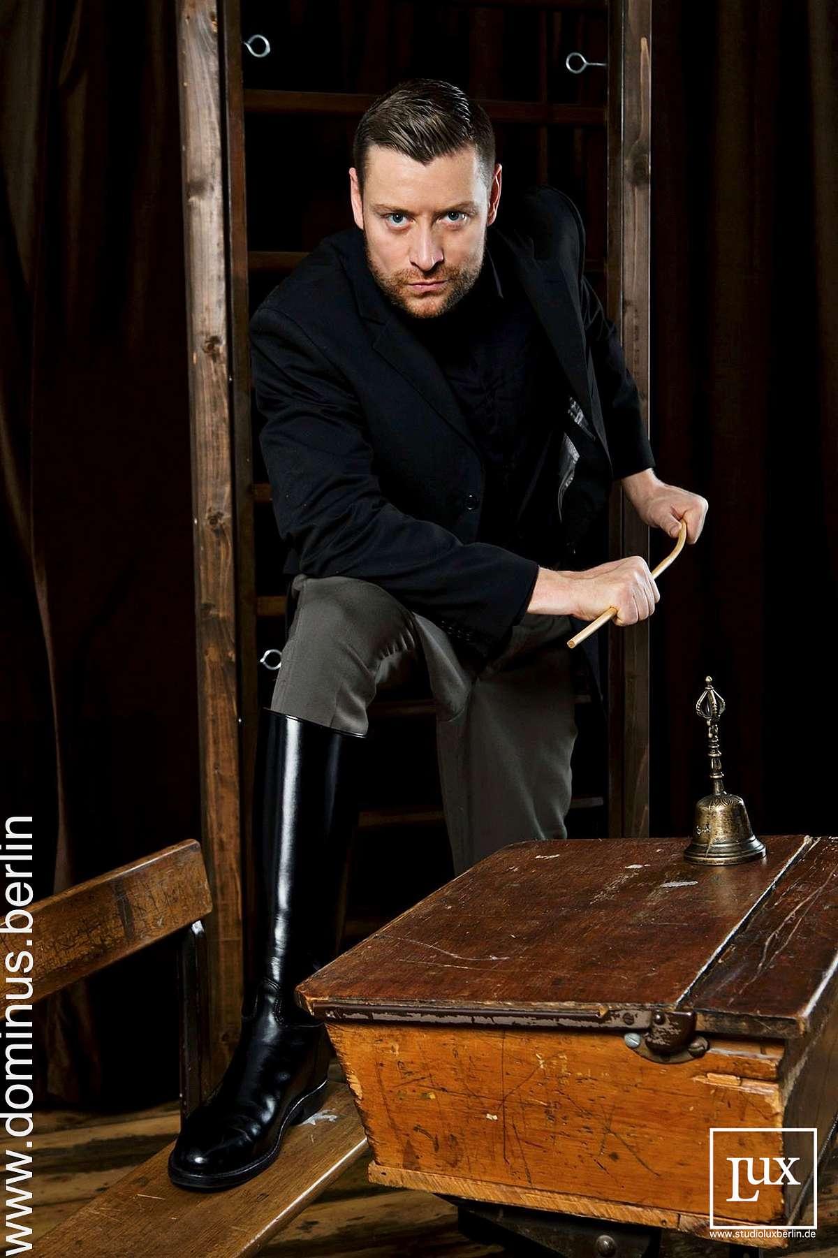SM Master Dominus.Berlin alias Master Andre in Lehrer Pose mit Schreibtisch Leder Stiefel und Schlagstock bereit fuer Bestragung bei Schueler