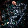 BDSM Ausdruck mit Master Andre alias Dominus Berlin in Vollleder auf einem Bett sitzend im Fetisch und Domina Studio Alter Bizarrer Bahnhof Duisburg