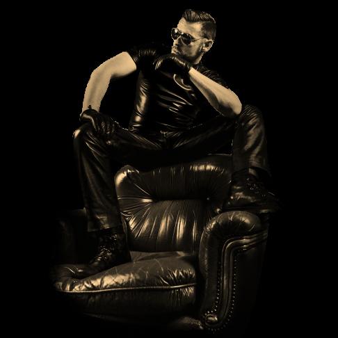 SM Master Dominus.Berlin alias Master Andre mit Lederhose, Lederhemd und Sonnenbrille bereit für Fetisch Aktion auf einem Sessel hockend