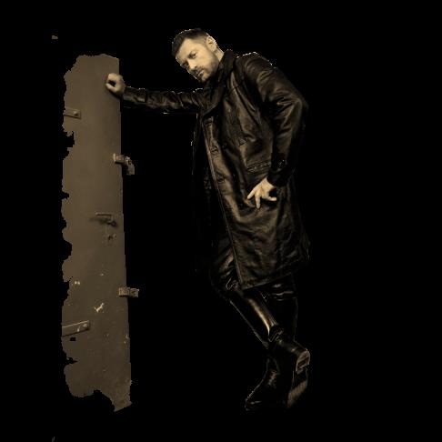 SM Master Andre alias DominusBerlin in Lederuniform und mit Ledermantel vor einer Kellertuer stehend