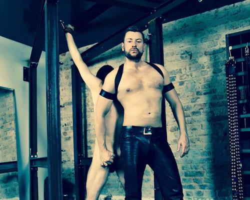 Master Andre alias Dominus Berlin im Stahlraum Studio Lux Berlin mit Lederhose und freiem Oberkoerper mit gefangenem Sklaven bereit für SM Spiel und Auspeitschung