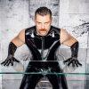 BDSM Master Andre alias DominusBerlin in Latexoutfit und mit Handschuh aus Latex an einem Tisch aus Plexiglas stehend