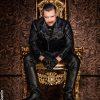 SM Master Andre alias DominusBerlin in voller Lederuniform frontal auf einem goldenen Thron sitzend in einem brauen Ambiente